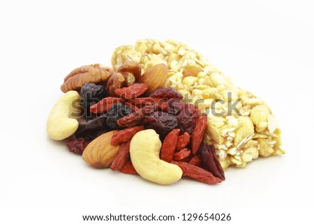 Healthy breakfast of nuts and dried fruits on white background. - stock photo