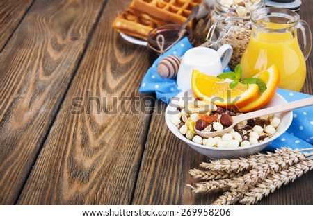 Healthy breakfast of oatmeal,wafers, fresh juice, jam and oranges on a wooden background - stock photo
