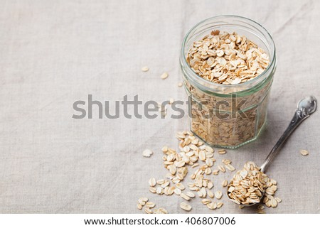 Healthy breakfast Organic oat flakes in a glass jar Grey textile background Copy space - stock photo