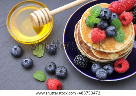 Healthy Breakfast.Pancakes with berries and honey.