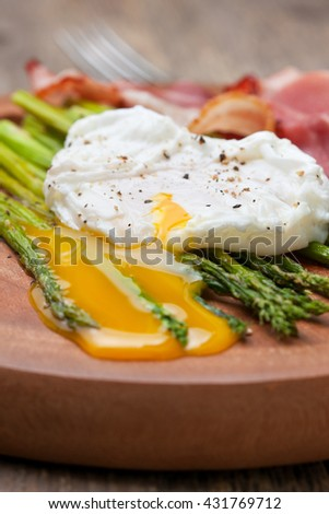 healthy breakfast: poached egg, baked asparagus on a wooden background close up - stock photo