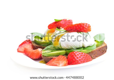 Healthy Breakfast:Poached egg on piece of rye bread with Avocado slices,Spinach and Strawberry . - stock photo