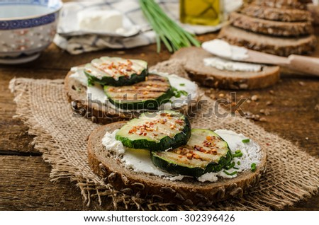 Healthy breakfast - seeds bread spread by cream cheese and grilled zucchini and chilli flakes, with chive - stock photo