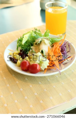 Healthy breakfast set, Fresh vegetable salad and orange juice. - stock photo