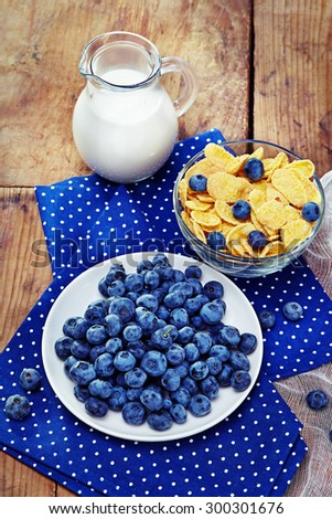Healthy breakfast with corn flakes, berries, milk on wooden background  blueberry - stock photo