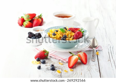 Healthy breakfast with cornflakes and fresh berries on white wooden background, selective focus - stock photo