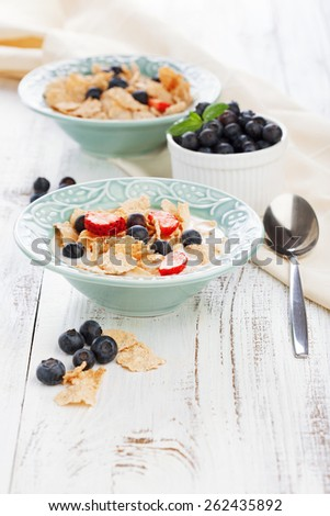 Healthy breakfast with cornflakes, milk and fresh berries on white wooden background