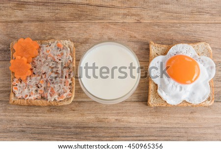 Healthy breakfast with fried egg,sandwich and milk on wooden table