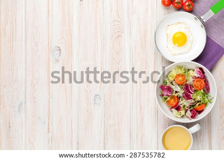 Healthy breakfast with fried egg, tomatoes and salad on white wooden table. Top view with copy space - stock photo