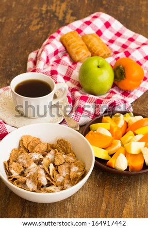 Healthy breakfast with granola, fruits, nuts and coffee.