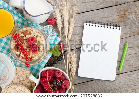 Healthy breakfast with muesli, berries and orange juice. View from above on wooden table with notepad for copy space - stock photo