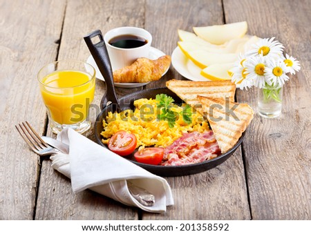 healthy breakfast with scrambled eggs, juice and fruits on wooden background - stock photo