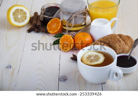 Healthy breakfast with tea, croissant, tangerines, jam, milk and honey on wooden background - stock photo