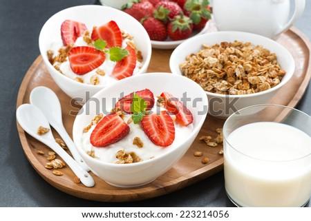 healthy breakfast - yogurt, fresh strawberries, granola and milk on wooden tray, horizontal - stock photo