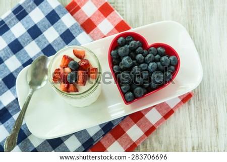 Healthy breakfast yogurt with blueberries in heart shaped bowl and strawberries