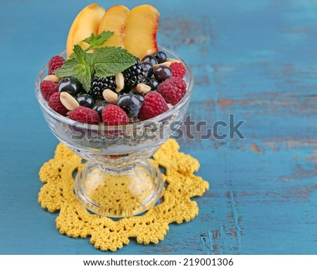 Healthy breakfast - yogurt with  fresh fruit, berries and muesli served in glass bowl on color wooden background - stock photo