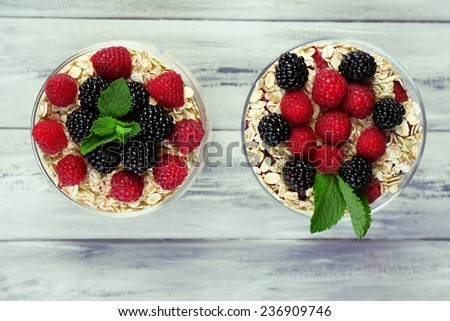Healthy breakfast - yogurt with  fresh fruit, berries and muesli served in glass jar and bowl, on color wooden background - stock photo