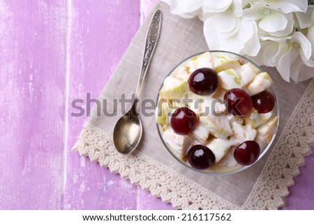 Healthy breakfast - yogurt with  fresh grape and apple slices and muesli served in glass bowl, on color  wooden background - stock photo
