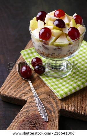 Healthy breakfast - yogurt with  fresh grape and apple slices and muesli served in glass bowl, on wooden background - stock photo