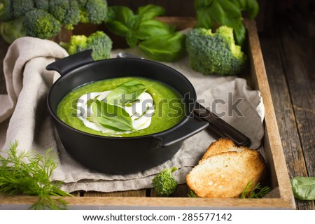 healthy broccoli cream soup on rustic background - stock photo