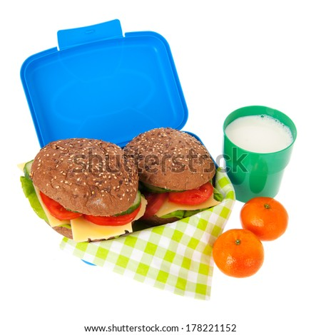 Healthy brown bread rolls in blue lunch box with fruit and milk isolated over white background - stock photo