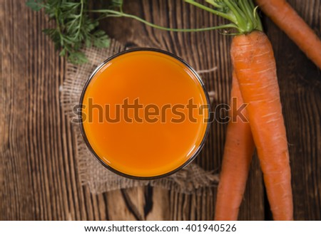 Healthy Carrot Juice (selective focus) on wooden background (close-up shot) - stock photo