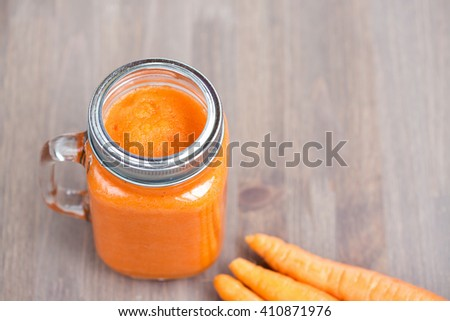 Healthy carrot smoothie in a jar with tube on wooden background - stock photo