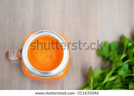 Healthy carrot smoothie in a mason jar with green parsley on wooden background. Shallow dof - stock photo