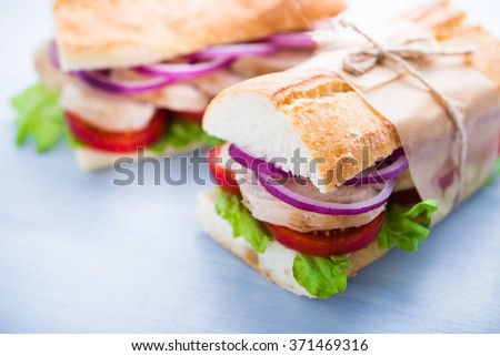Healthy chicken sandwiches with lettuce salad, tomato and onion on blue wooden background close up. - stock photo