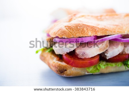 Healthy chicken sandwiches with lettuce salad, tomato and onion on blue wooden background close up. Healthy food. - stock photo