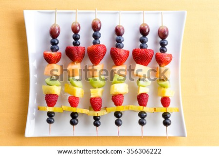 Healthy colorful fresh shish kebab fruit treats made from seasonal summer tropical fruit arranged neatly in a row on a modern white rectangular platter on a yellow textured table viewed from above - stock photo