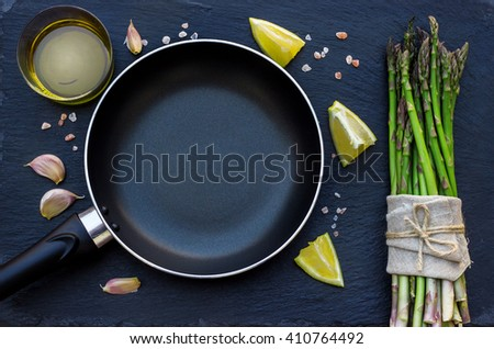 Healthy concept. Bunch of organic fresh asparagus with ingredients for cooking and frying pan on a grunge stone table. Selective focus, copy space background, flat lay - stock photo