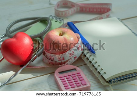 Healthy concept. Diet plan, health check, weight control and body mass index calculation with opened notebook, pen, heart, stethoscope, apple, calculator and measuring tape on white wooden background