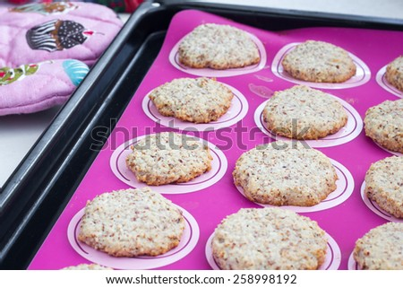 Healthy cookies fresh out of the oven on a pink baking sheet in the pan. - stock photo