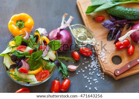 Healthy cooking salad with fresh delicious ingredients making on cutting board. Diet or vegetarian food concept.