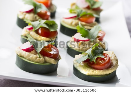 Healthy cucumber hummus bites with tomato, radish and cilantro.