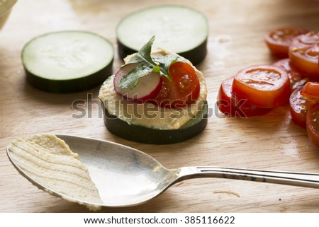 Healthy cucumber hummus bites with tomato, radish and cilantro on cutting board with spoon. - stock photo