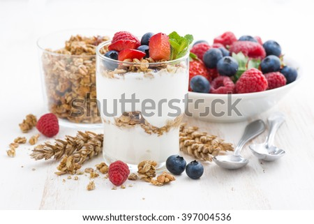 healthy dessert with natural yogurt, muesli and berries on a white background, closeup, horizontal - stock photo