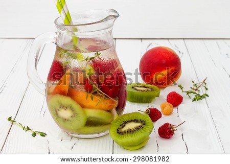 Healthy detox fruit infused flavored water. Summer refreshing homemade cocktail with fruits and thyme on white wooden table - stock photo