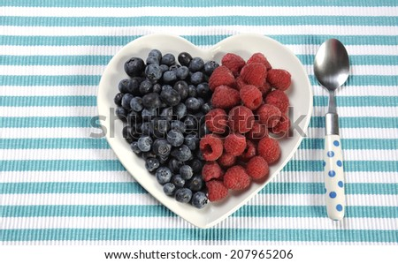 Healthy diet high dietary fiber breakfast with blueberries and raspberries in heart shape white plate on aqua blue stripe place setting. - stock photo