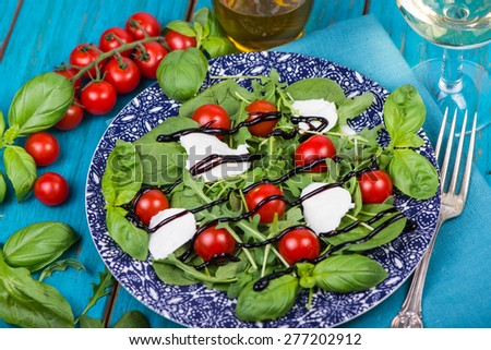 Healthy diet salad with tomatoes, mozzarella,basil and balsamic vinegar on plate - stock photo