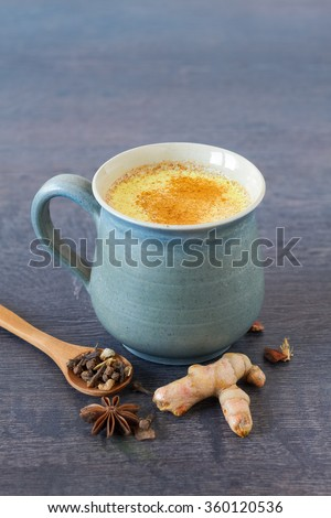 Healthy drink made from turmeric roots, exotic spices  with milk and honey - stock photo