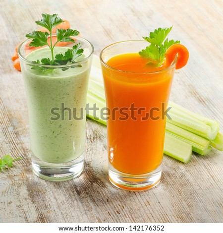 Healthy drinks - Green vegetable smoothie and carrot juice  on a wooden table. selective focus
