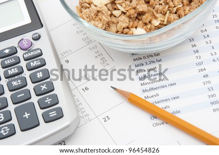 Healthy eating concept - calendar with daily nutrition intake, nutrition chart, muesli in glass bowl and calculator. - stock photo