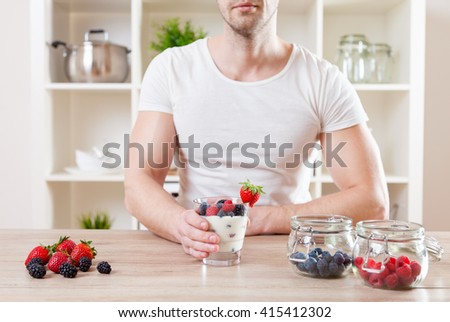 Healthy eating concept. Closeup on man with delicious yogurt with fresh berries - stock photo