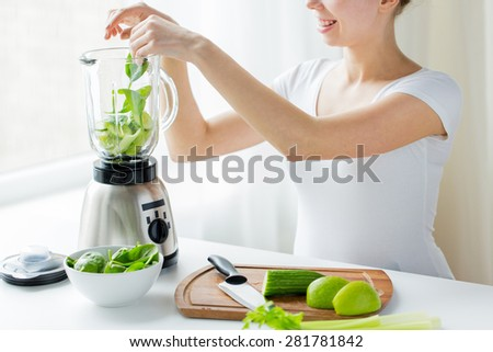 healthy eating, cooking, vegetarian food, dieting and people concept - close up of young woman with blender and green vegetables making detox shake or smoothie at home - stock photo