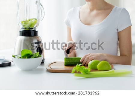 healthy eating, cooking, vegetarian food, dieting and people concept - close up of young woman with blender chopping green vegetables for detox shake or smoothie at home - stock photo