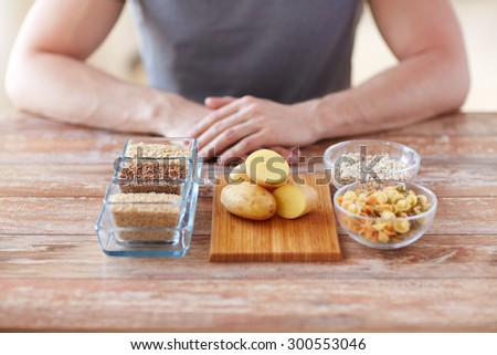 healthy eating, diet and people concept - close up of male hands with carbohydrate food on table - stock photo