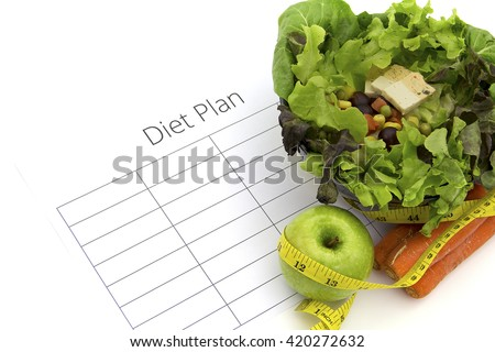 healthy eating, dieting, slimming and weigh loss concept - close up of diet plan paper green apple, carrot, measuring tape and salad - stock photo