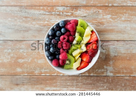 healthy eating, dieting, vegetarian food and people concept - close up of fruits and berries in bowl on wooden table - stock photo